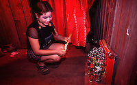 Phnom Penh, Cambodia. Burning incense at a shrine inside a brothel to appease the gods. Condom packets lie on floor. Teenaged prostitute in brothel in Tuol Kork district. The girls here make US$30 a month, working on average 6 clients a day. <br />