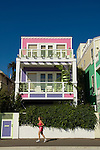 A jogger on the Santa Monica bike path runs past a colorful beach house