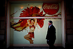 A man walks in front of posters from the Coca Cola Company building in 5th Ave. Coca Cola Company management will discuss its final quarterly results for 2011 on February 7th at the New York Stock Exchange, New York, USA.  January 3, 2012. Photo by Eduardo Munoz Alvarez / viewpress