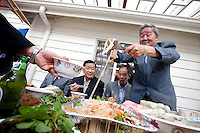 Guests enjoy a feast following the tea ceremony and marriage of Caroline and San in Seattle. (Photo by Dan DeLong/Red Box Pictures)