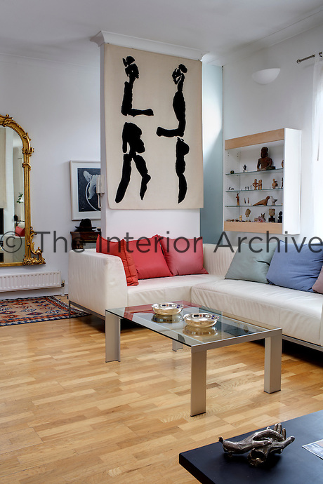 The large open plan living area contains a comfortable L-shaped sofa with a large black-and-white tapestry hanging above and a glass vitrine is the repository for  an intriguing collection of small sculptural works