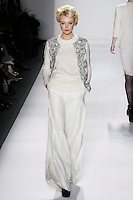 Model walks runway in an ivory handloomed cashmere/silk twinset bordered w/ivory+black reembroidered french lace sprinkled w/ombre beads, and ivory loro piana wool/angora a-line trouser, from the Zang Toi Fall 2012 &quot;Glamour At Gstaad&quot; collection, during Mercedes-Benz Fashion Week New York Fall 2012 at Lincoln Center.
