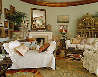 A 19th century painted Italian daybed has a Fortuny fabric draped over the seat