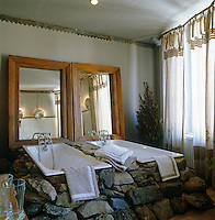 Pair of bath tubs encased in a pile of loose boulders with a pair of rustic mirrors against the wall behind them