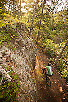 A mountain biker rides below a rock wall on The Flow trail of Copper Harbor Michigan.