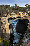 Tasman's Arch is a natural arch which is really a huge cave running from the coast along a zone of closely spaced cracks and extending inland to a second zone perpendicular to the first. The roof at the landward end of the tunnel has collapsed from the power of the ocean's waves..