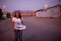 A woman walks down the street on Tuesday, Apr. 7, 2009 in Ventanilla, Peru.