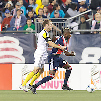 New England Revolution substitute forward Dimitry Imbongo (92) dribbles down the wing as Columbus Crew defender Tyson Wahl (2) defends. In a Major League Soccer (MLS) match, the New England Revolution (blue) defeated Columbus Crew (white), 3-2, at Gillette Stadium on October 19, 2013.
