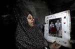 A Palestinian woman holds a picture of the Dhuheir three children, who were killed after a fire swept through their house in Gaza City on January 31, 2013. Hazem Dheir, his wife Sahar and their four young children were killed in the fire that is believed to have started by an electrical faul. Photo by Ashraf Amra