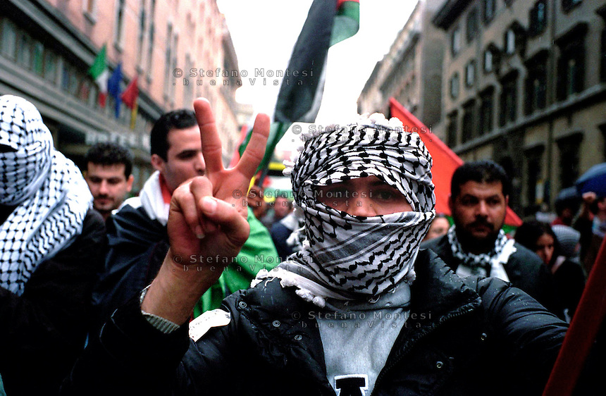 Roma  2004 .Manifestazione per la Palestina.Un uomo  con la kefia fa il segno della  vittoria.Rome 2004.Demonstration for Palestine.A man with kafeeyah  makes the sign of victory
