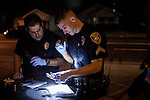Stockton Police officers James Padilla, left, and Chris Martin, center, inspect a handgun found on a mourner at the site of a memorial for five people shot the night before in Stockton, California, September 18, 2013. Facing stark and rising homicide rates, the California cities Oakland and Stockton are taking a second chance at a novel method of disrupting street gangs, called Ceasefire, in which the police use social-analytics software to map out connections between a city's most violent gang members, using the data to make targeted and coordinated arrests.