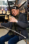 Music instrument store owner in Shanghai, China plays Erhu Chinese fiddle