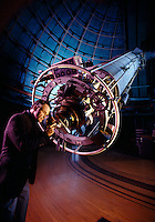 Man looking through an observatory telescope.