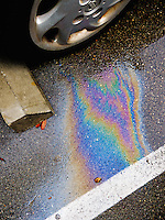 Rainbow colors of spilled oil on wet pavement next to a parked car.