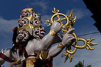Ogoh-Ogoh (demon) sculpture of Dasamuka (Rahwana, major evil spirit in Ramayana-story)or Butha siwu / Bhuta Siu (opposite pair of giants in classic balinese wayang kulit pantheon) holding  typical balinese and tantra hindu chakras / magic items, which they use to fight each other, Bedulu near Ubud, Central Bali. Balinese New Year called Nyepi (around march according to lunar calendar),  is a silent day of meditation and spiritual purification. One day before exorcist rituals are held for purification and balance of polar powers of the universe, first at noon by a priest (exorcism called Caru or Tawur Agung) and later on after sunset in a popular, carneval-like procession of Ogoh-Ogoh, symbolizing bhuta kali (demon, bad spirits,bad habits),  so all the bad spirits leave the village and the island.  Loud, rhythmic music and special performances are part of the procession called Ngerupuk. Road crossings are major spots of exorcism and special ogoh-ogoh performance, since demons often like to dwell here. At Nyepi, the following day, there is 24 hours silence, no vehicle or people on the street, no light or fire, no working - all the bad spirits should think, the island is abandoned and leave the island. Day after Nyepi is a day of reconciliation - new year starts purified.