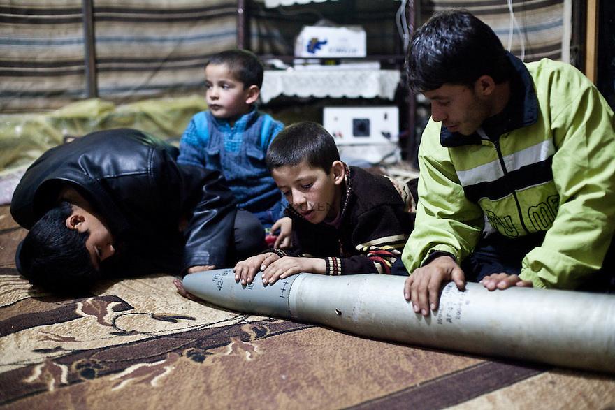 Teenagers are observing a rocket coming from a tank of the regular army. The FSA brought it to their father who use to repai weapons and bombs. .Des adolescents sont en train d'observer une rocket provenant d'un tankde l'armée régulière. La FSA a apporté à leur père qui l'utiliser pour réparer des armes et des bombes.