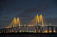 The Fred Hartan bridge after dark with the lights on giving it a golden glow against the night sky.  The bridge span 2.8 miles across the ship channel from  La Porte to Baytown Texas.  The bridge was built to replace the tunnel that went underneath the water so they could dig it out for bigger ships to pass. You can cleary make out the refinery underneath the bridge even the fracking flare.