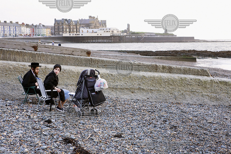 An Hasidic couple and their baby spend the afternoon on the beach in Aberystwyth.