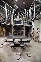 Guards stand around the TV room of Camp 6. Detainees are shackled to the floor while they watch TV at the American naval base at Guantanamo Bay, where over 600 alleged al Qaeda members have been held indefinitely. Described by the US as 'unlawful enemy combatants', they were captured primarily in Afghanistan during the 'war against terror'.