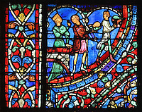 A courtesan gives orders to 2 servants to take food to the table, from The Feast in the Brothel, from the Parable of the Prodigal Son stained glass window, in the north transept of Chartres Cathedral, Eure-et-Loir, France. This window follows the parable as told by St Luke in his gospel. It is thought to have been donated by courtesans, who feature in 11 of the 30 sections. Chartres cathedral was built 1194-1250 and is a fine example of Gothic architecture. Most of its windows date from 1205-40 although a few earlier 12th century examples are also intact. It was declared a UNESCO World Heritage Site in 1979. Picture by Manuel Cohen