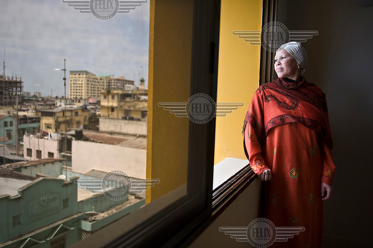 Madame Al-Shaymaa J. Kwegyir, Tanzania's first albino Member of Parliament looks out over Dar es Salaam from her apartment window. The nomination of an albino MP is a first step in the fight against the widespread belief that albinism is the result of a curse. Discrimination against albinos is a serious problem throughout sub-Saharan Africa, but recently in Tanzania albinos have been killed and mutilated, victims of a growing criminal trade in albino body parts fuelled by superstition and greed. Limbs, skin, hair, genitals and blood are believed by witch doctors to bring good luck, and are sold to clients for large sums of money, carrying with them the promise of instant wealth.