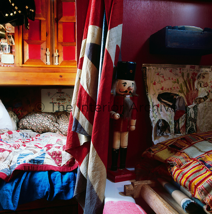 The cosy interior of a canal boat decorated in a bohemian style. A detail of the sleeping area