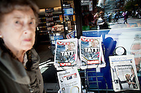 Oslo, Norway, 23.07.2011. A norwegian elderly lady observes Norwegian newspapers headlines &quot;Caught!&quot;. On 22 July 2011, Anders Behring Breivik bombed the government buildings in Oslo, which resulted in eight deaths. He then carried out a mass shooting at a camp of the Workers' Youth League (AUF) of the Labour Party on the island of Ut&oslash;ya where he killed 69 people, mostly teenagers. Photo: Christopher Olss&oslash;n. ..----------------------------..-ITALY OUT-..----------------------------