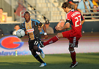 CHESTER, PA - AUGUST 12, 2012:  Freddy Adu (11) of the Philadelphia Union watches  Arnie Friedrich (23)  of the Chicago Fire kick the ball away during an MLS match at PPL Park, in Chester, PA on August 12. Fire won 3-1.