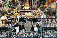 Antiques and jewels of Tibet and Nepal origin on sale in antique shop window in Staalstraat in the Old Town, Amsterdam, Holland
