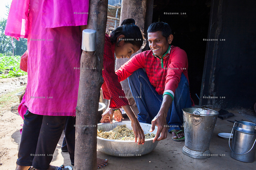 Dhiraj Khristi, 36, and his daughter (center) prepare food for their buffaloes at their farm house in Anand, Gujarat, India on 9th December 2012. Dhiraj's sister had convinced his wife Pinki to become a surrogate together in 2008 and Pinki has since done 2 surrogacies. While the couple used to make 2000-5000 rupees per month from farming and as labourers, she had made over 850,000 from both her surrogacies and had bought land, buffaloes and saved 320,000 rupees in a fixed deposit. They have both also convinced other villagers to become surrogates and earned a small amount from a successful introduction to Dr. Nayana Patel resulting in pregnancy. Photo by Suzanne Lee / Marie-Claire France