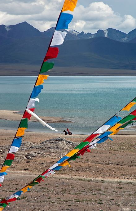 Prayer Flags  and a Horse Rider Tibetan Nomad at Lake Namtso, a Holy Lake for Tibetans at an elevation of 4800 meters and the highest saltwater lake in the world.