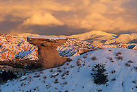 Camel Rock,a colorful earth formation north of Santa Fe, basks in the momentary winter alpenglow from the snow covered Sangre de Cristo mountains