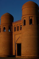 General view of  Ota Darvoza (Father Gate), main gate to Ichan Kala,  Khiva, Uzbekistan, pictured on July 6, 2010, at sunset. Khiva's old city, Ichan Kala, is surrounded by 2.2 kilometres of crenellated and bastioned city walls. Some sections may be 5th century, but the strongest sections were built 1686-88 by Arang Khan. The main gate today is the restored western Ota Darvoza (Father Gate). Khiva, ancient and remote, is the most intact Silk Road city. Ichan Kala, its old town, was the first site in Uzbekistan to become a World Heritage Site(1991). Picture by Manuel Cohen.