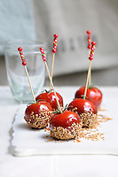 Cocktail tomatoes dipped in caramel and garnished with sesame seeds