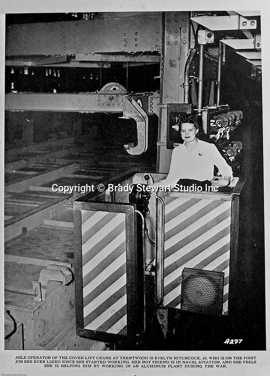 Spokane Washington and McCook Illinois: View of Swindell-Dressler brochure highlighting the Electric Furnaces designed, constructed and installed in two Alcoa plants during World War II.  The caption reads:  Able operator of the cover-lift crane at Trentwood is Evelyn Hitchcock, 20.  Who is on the first job she ever liked since she started working.  Her boy friend is in Naval Aviation, and she feels she is helping him by working in an Aluminum plant during the war.