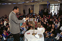 RABBI CELEBRATES HANUKKAH IN CEREMONY FOR YOUNG CONGREGANTS OF SYNAGOGUE. JEWISH FAMILY. SAN FRANCISCO CALIFORNIA.