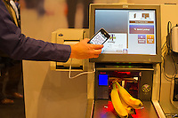 00091686 New York, New York.  1/16/2012 NATIONAL RETAIL FEDERATION TRADE SHOW. IBM demonstrates their self-checkout  scanner system, using a smartphone at the IBM booth at the annual National Retail Federation trade show at the Jacob Javits Convention Center in New York    FRANCES ROBERTS/FREELANCE PHOTOGRAPHER