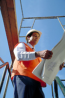 Native American engineer studies building plans at a bridge jobsite, Sacramento, CA