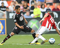 Andy Najar #14 of D.C. United  shovels the ball away from Blair Gavin #18 of Chivas USA during an MLS match at RFK Stadium, on May 29 2010 in Washington DC. United won 3-2.