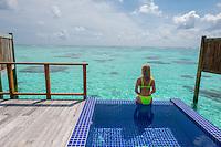 Maldives, Rangali Island. Conrad Hilton Resort. Woman in ocean villa swimming pool near the water. (MR)