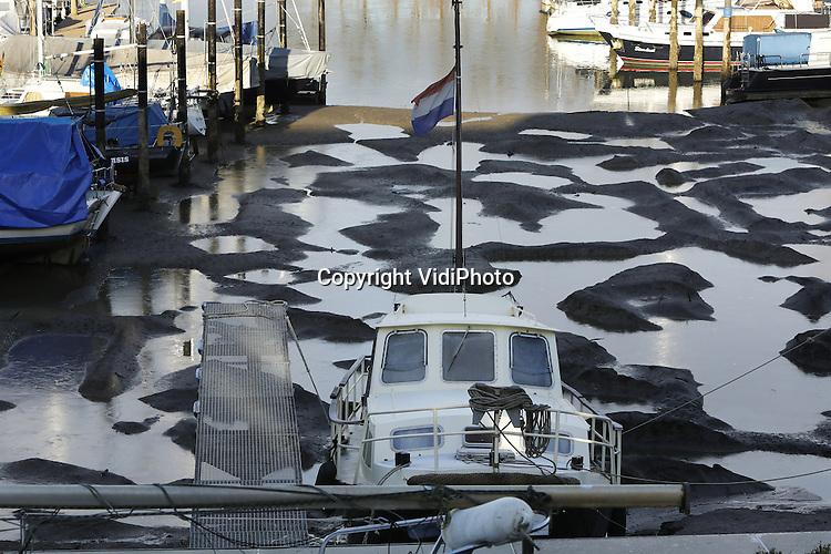Foto: VidiPhoto<br /> <br /> GRAVE - Georganiseerde chaos donderdag in de jachthaven van Grave aan de Maas. De meeste boten liggen droog. Door de stukvaren van de stuw bij Grave, veroorzaakt door een Duits schip, is het water op de Maas zo'n 3 meter gezakt. De jachten in het haventje van Grave zijn daardoor vastgeraakt in de modder. Hoe groot de schade aan de boten is, is nog niet duidelijk. Doordat de bodem niet uit stenen, maar uit slik bestaat lijkt die mee te vallen. De schade aan de stuw lijkt onherstelbaar. De binnenvaartsector lijdt zo'n 3 ton schade per dag doordat schepen nu moeten omvaren. Ook het Maaswaal-kanaal is gestremd door het lage water. Voor de sluizen bij Weurt liggen 25 binnenschepen te wachten tot er voldoende water in het kanaal is gepompt.