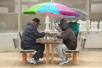 Two men play chess during a rainy day at Santa Monica Chess Park on Sunday, January 6, 2008.