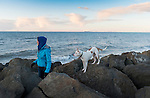 A girl and her dog at the water to watch the sunset, on the rip-rap seawall rocks on Ediz Hook. The Hook is the spit sandbar which creates Port Angeles Harbor, in the Strait of Juan de Fuca.