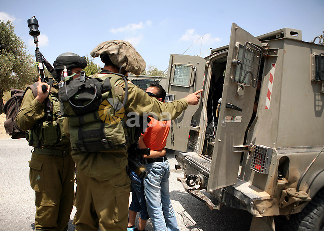 Israeli soldiers detain Palestinian child during clashes in the West  Bank village of Nabi Saleh, on 28 May 2010. Palestinians protest weekly against the neighbouring Jewish settlement of Halamish. photo by Eyad Jadallah