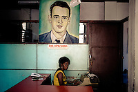 A Cuban office worker types under a painted portrait of the revolutionary leader and poet Raul Gomez Garcia, hung on the wall of the Cuban state office in Santiago de Cuba, Cuba, 5 August 2008. During the Cuban Revolution, an armed rebellion at the end of the 1950s in Cuba, most of the revolutionary leaders started as no-name soldiers fighting in the jungle. Although the revolutionary leaders, after taking over the power, became autocratic rulers holding almost absolute power and putting the opposition in jail, for some reason Cuban people have never stopped to worship Fidel Castro, Che Guevara, Raul Castro and others. Cubans hang their photos and portraits on the wall in homes, shops and working places even they don't have to. The people of Cuba love their heroes.