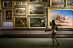 "Jasmine Sotoodeh views paintings in the ""salon"" room at the Crocker Art Museum in Sacramento, California."