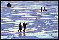 ICE FISHERMEN ARE SILHOUETTED AGAINST POLISHED ICE REFLECTING THE SKY AT DUSK ON TEAL LAKE IN NEGAUNEE MICHIGAN.