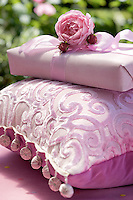 A present wrapped in plain pink paper and ribbon balances on a pink cushion