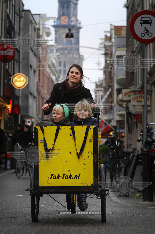 Jennifer Walker ferries her two sons Sam (left) and Nathaniel to and from their elementary school in a carrier cycle, a massively popular means of transport for parents in Amsterdam..