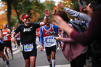 A runner check hands with his friends as he attends the annual TCS New York City Marathon in Central Park New York 01.11.2015. Mary Keitany wins second consecutive NYC Marathon, Stanley Biwott is men's winner. Ken Betancur/VIEWpress.